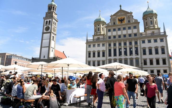 Die Friedenstafel auf dem Rathausplatz ist ein zentraler Bestandteil des Augsburger Hohen Friedensfestes, das seit 1650 jedes Jahr am 8. August gefeiert wird und jetzt ein deutsches immaterielles Kulturerbe ist. Bildnachweis: Ruth Plössel/Stadt Augsburg